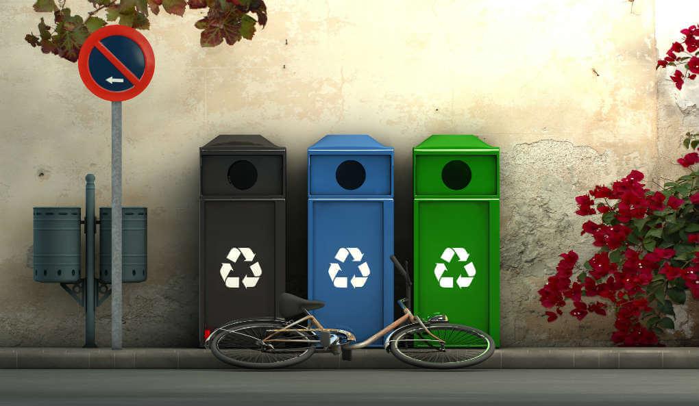 rua com três lixeiras para reciclagem