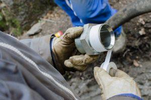 homem faz manutenção em porca de cano de abastecimento de água