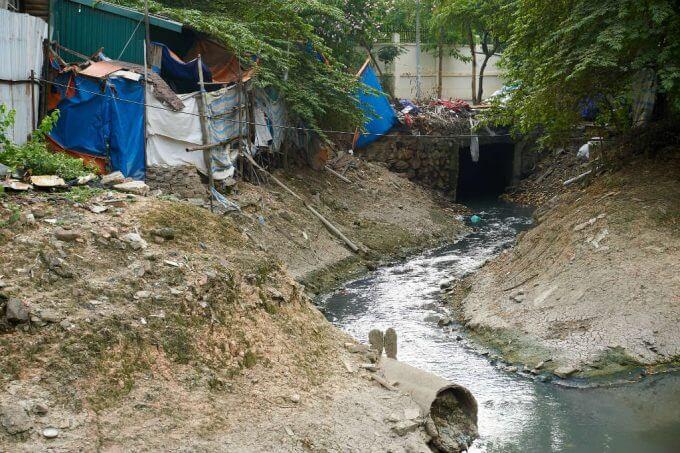 corrego com agua suja favela