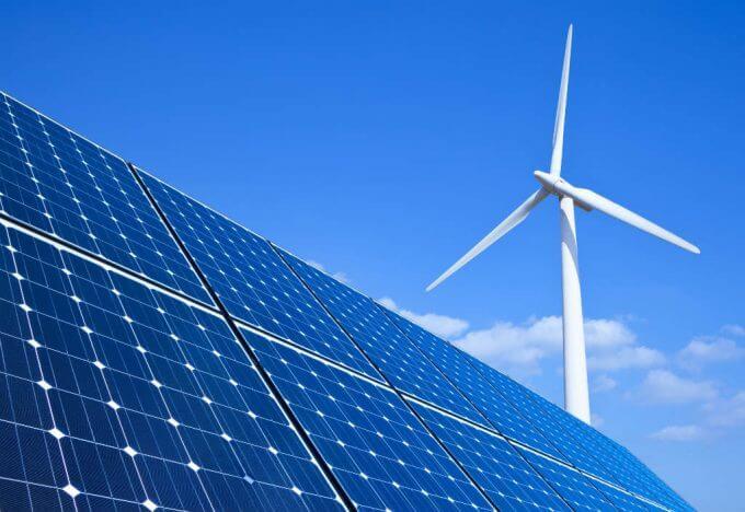 painel solar em primeiro plano com turbina eólica ao fundo