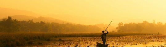 Homem rema em meio à água poluída. Crédito: Asif Aman/Unsplash