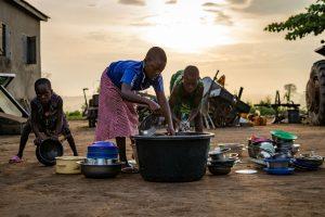 Crianças africanas lavam louça com pouca água. Crédito: Jordan Rowland/Unsplash